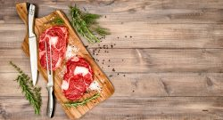 Rib Eye Steak with herbs and spices on wooden kitchen desk. Food background